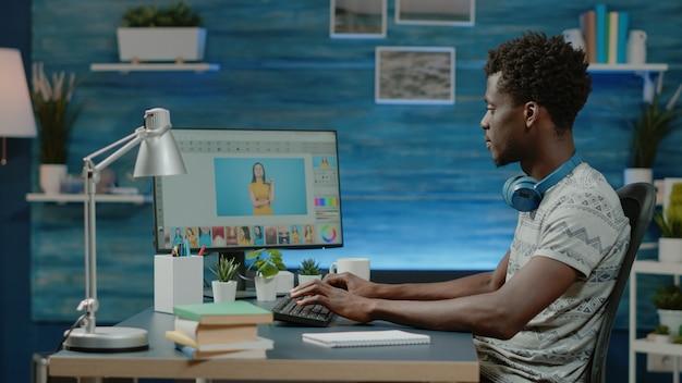 Afroamerikanischer fotograf, der bilder auf dem computer retuschiert