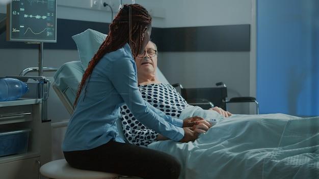 Afroamerikanischer freund besucht älteren patienten in der krankenstation