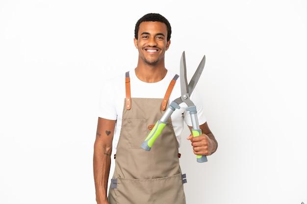 Afroamerikanischer gärtner, der eine gartenschere über isoliertem weißem hintergrund hält und mit armen an der hüfte posiert und lächelt