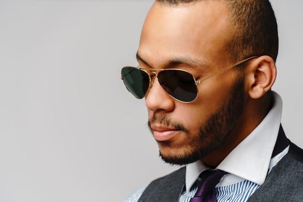 Afroamerikanischer geschäftsmann, der brillenporträt über grau trägt.