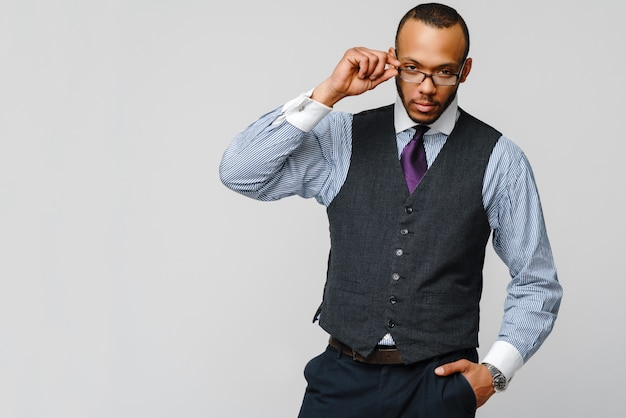 Afroamerikanischer geschäftsmann, der brillenporträt über grauer wand trägt