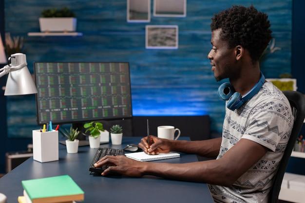 Afroamerikanischer geschäftsmann, der das börsendiagramm auf dem computer analysiert