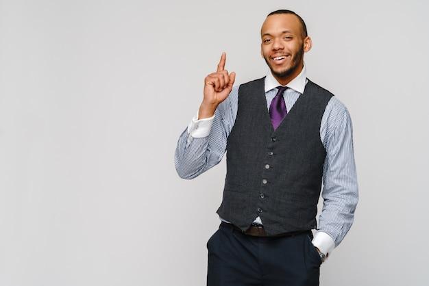 Afroamerikanischer geschäftsmann, der durch finger über grau auftaucht.