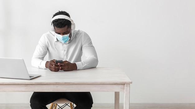 Afroamerikanischer geschäftsmann, der medizinische maske trägt