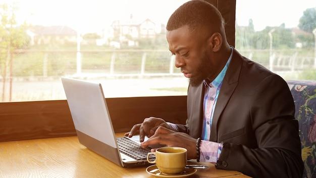 Afroamerikanischer geschäftsmann gibt eine nachricht auf dem laptop ein, der im sommercafé in der nähe des fensters sitzt. schwarzer mann schreibt auf computer, sonnenlicht. er trägt hemd und anzugjacke. arbeiten mit einer tasse kaffee.