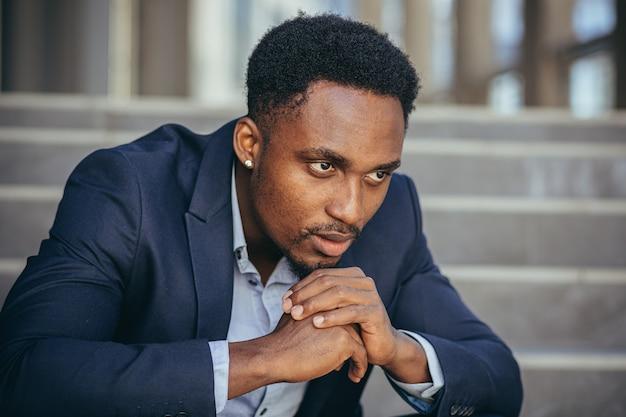 Afroamerikanischer geschäftsmann im business-anzug frustriert bekam schlechte nachrichten von der arbeit, feuerte deprimiert auf der treppe sitzend, nahaufnahme-porträtfoto