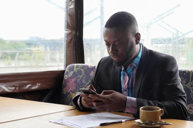 Afroamerikanischer geschäftsmann tippt eine nachricht auf dem smartphone