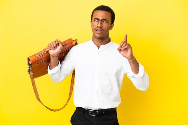Afroamerikanischer geschäftsmann über isolierter gelber oberfläche, der eine idee denkt, die mit dem finger nach oben zeigt
