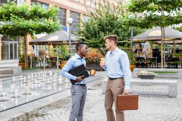 Afroamerikanischer geschäftsmann und ein kaukasischer geschäftsmann diskutieren und trinken kaffee auf stadt, kaffeepause