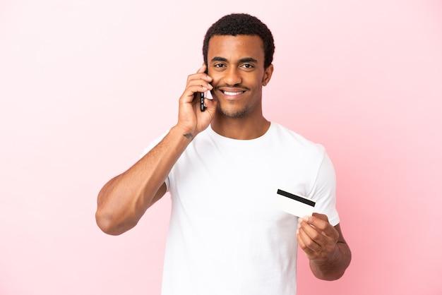 Afroamerikanischer gutaussehender mann auf isoliertem rosa hintergrund, der ein gespräch mit dem mobiltelefon führt und eine kreditkarte hält