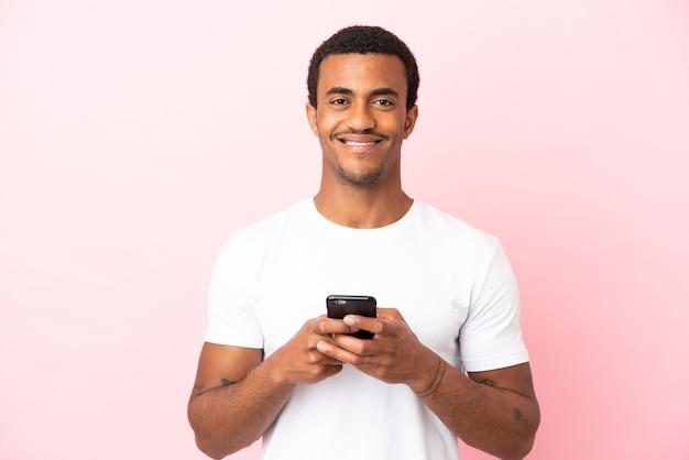 Afroamerikanischer gutaussehender mann auf isoliertem rosa hintergrund, der in die kamera schaut und lächelt, während er das handy benutzt