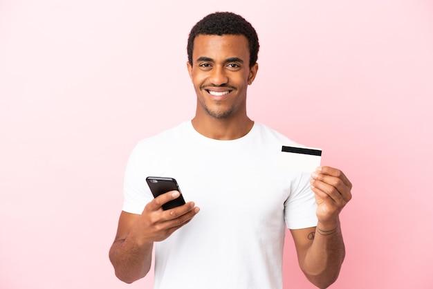 Afroamerikanischer gutaussehender mann auf isoliertem rosa hintergrund, der mit dem handy mit einer kreditkarte kauft