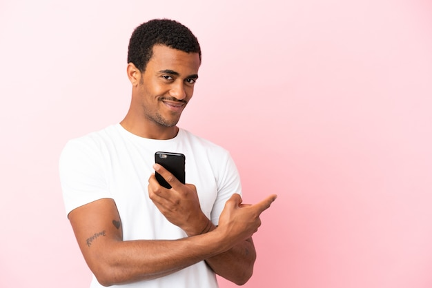 Afroamerikanischer gutaussehender mann auf isoliertem rosa hintergrund mit handy und nach hinten zeigend