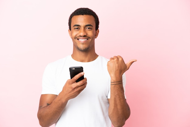 Afroamerikanischer gutaussehender mann auf isoliertem rosa hintergrund mit handy und zeigt auf die seitliche