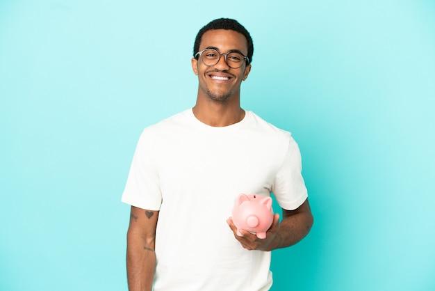 Afroamerikanischer gutaussehender mann, der ein sparschwein über isoliertem blauem hintergrund hält, der mit armen an der hüfte posiert und lächelt