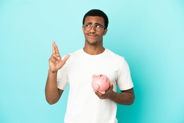 Afroamerikanischer gutaussehender mann, der ein sparschwein über isoliertem blauem hintergrund hält, die finger kreuzen und das beste wünschen