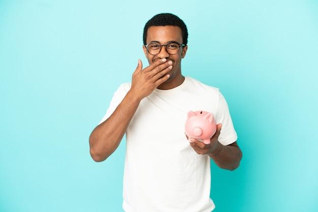 Afroamerikanischer gutaussehender mann, der ein sparschwein über isoliertem blauem hintergrund hält, glücklich und lächelnd, den mund mit der hand bedeckend