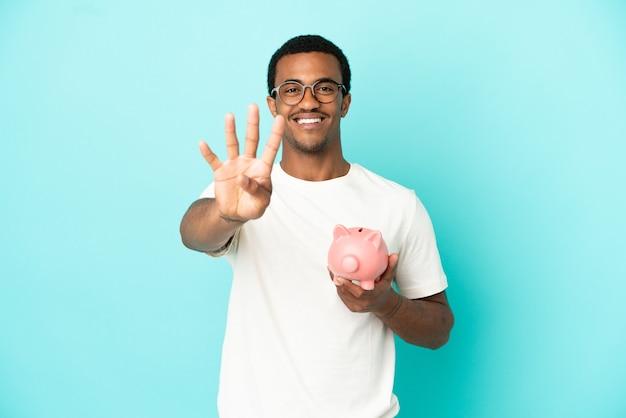 Afroamerikanischer gutaussehender mann, der ein sparschwein über isoliertem blauem hintergrund hält, glücklich und zählt vier mit den fingern