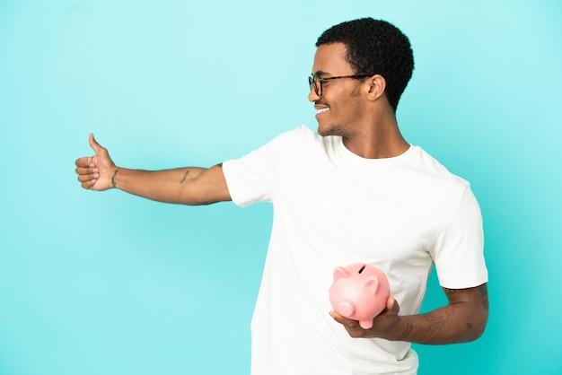 Afroamerikanischer gutaussehender mann, der ein sparschwein über isoliertem blauem hintergrund hält und eine geste mit dem daumen nach oben gibt
