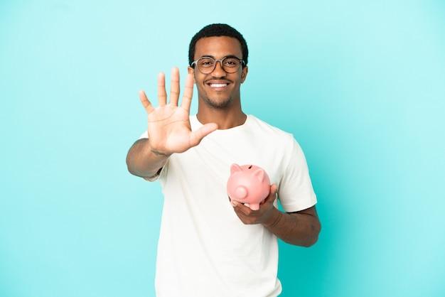 Afroamerikanischer gutaussehender mann, der ein sparschwein über isoliertem blauem hintergrund hält und fünf mit den fingern zählt