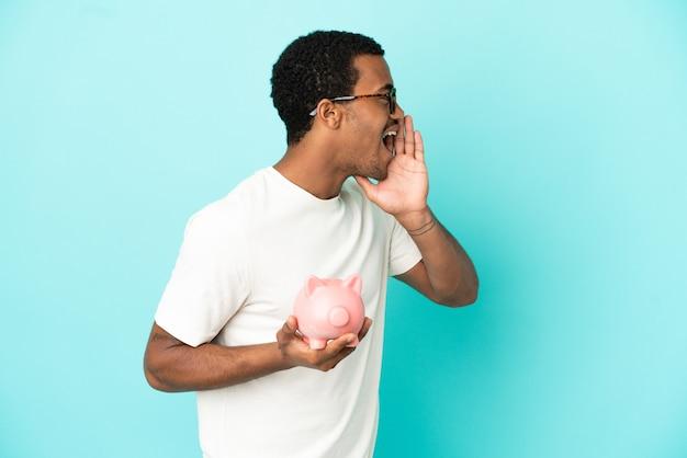 Afroamerikanischer gutaussehender mann, der ein sparschwein über isoliertem blauem hintergrund hält und mit weit geöffnetem mund zur seite schreit