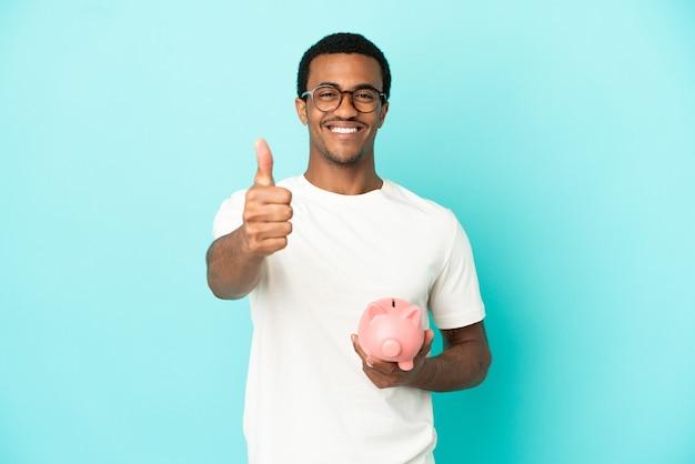 Afroamerikanischer gutaussehender mann, der ein sparschwein über isoliertem blauem hintergrund mit daumen nach oben hält, weil etwas gutes passiert ist