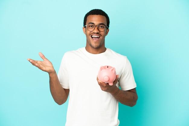 Afroamerikanischer gutaussehender mann, der ein sparschwein über isoliertem blauem hintergrund mit schockiertem gesichtsausdruck hält