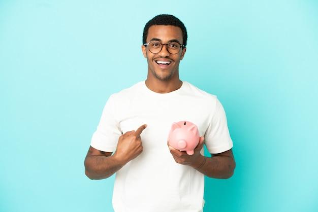 Afroamerikanischer gutaussehender mann, der ein sparschwein über isoliertem blauem hintergrund mit überraschendem gesichtsausdruck hält