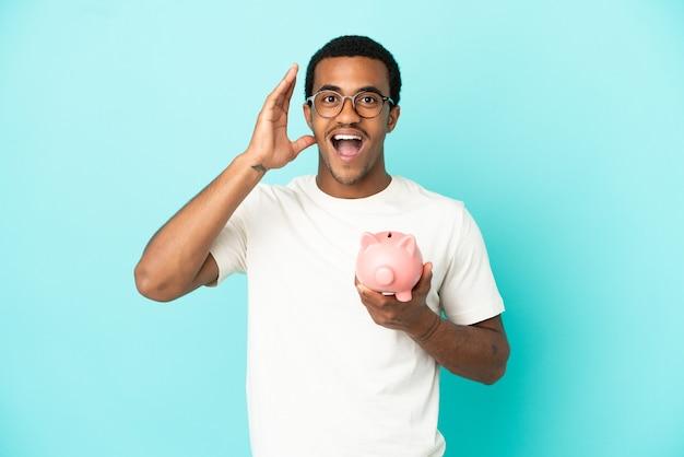 Afroamerikanischer gutaussehender mann, der ein sparschwein über isoliertem blauem hintergrund mit überraschung und schockiertem gesichtsausdruck hält