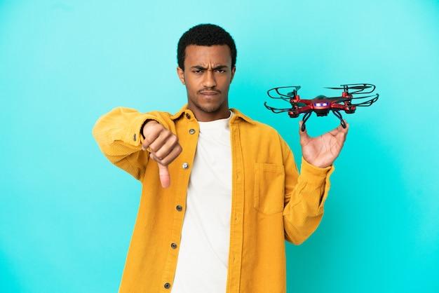 Afroamerikanischer gutaussehender mann, der eine drohne über isoliertem blauem hintergrund hält, der daumen nach unten mit negativem ausdruck zeigt