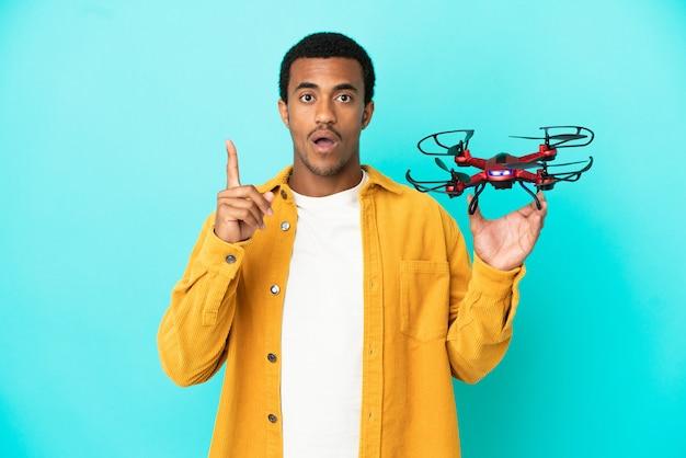 Afroamerikanischer, gutaussehender mann, der eine drohne über isoliertem blauem hintergrund hält und beabsichtigt, die lösung zu realisieren, während er einen finger hochhebt