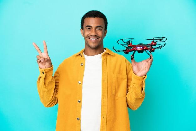 Afroamerikanischer gutaussehender mann, der eine drohne über isoliertem blauem hintergrund hält und lächelt und victory-zeichen zeigt