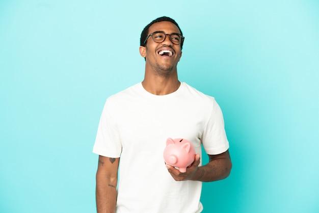 Afroamerikanischer gutaussehender mann mit einem sparschwein über isoliertem blauem hintergrund lachend
