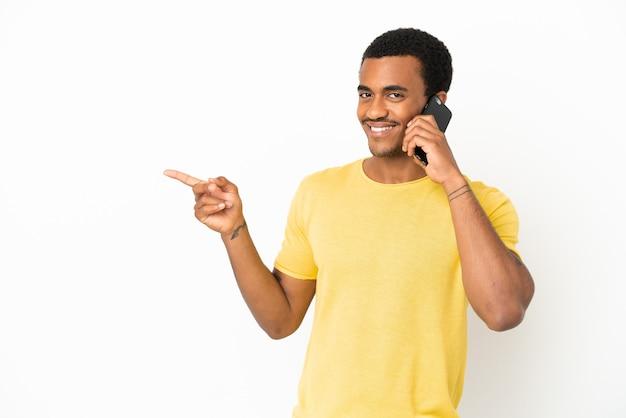 Afroamerikanischer gutaussehender mann mit handy über isoliertem weißem hintergrund, der mit dem finger zur seite zeigt