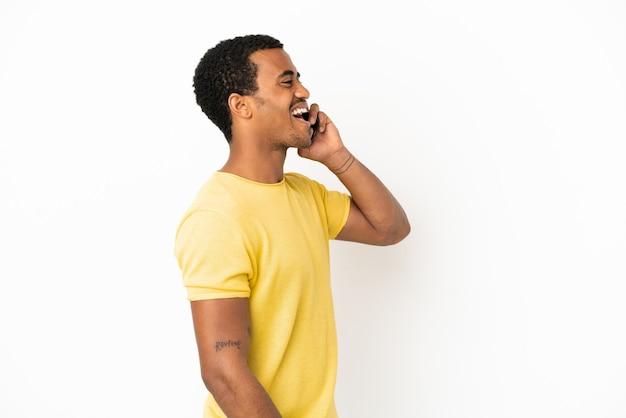 Afroamerikanischer gutaussehender mann mit handy über isoliertem weißem hintergrund lachend in seitenlage