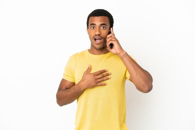 Afroamerikanischer gutaussehender mann mit handy über isoliertem weißem hintergrund überrascht und schockiert, während er nach rechts schaut