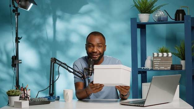 Afroamerikanischer influencer, der eine geschenkbox vor der kamera hält