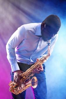 Afroamerikanischer jazzmusiker, der saxophon gegen buntes rauchiges spielt