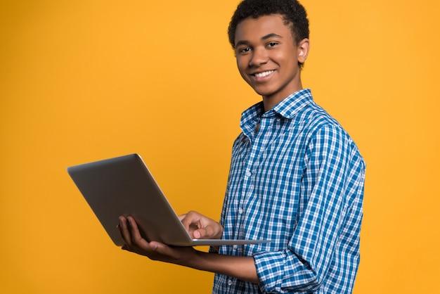 Afroamerikanischer jugendlicher, der mit laptop arbeitet.