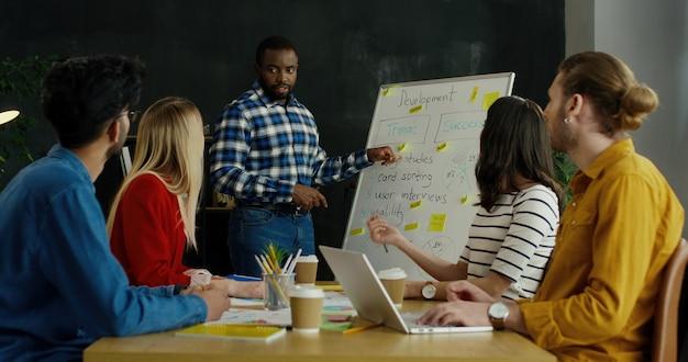 Afroamerikanischer junger mann beendet seinen bericht über unternehmensgründungsstrategie und applaudierende kollegen.