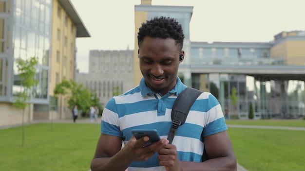 Afroamerikanischer junger mann, der das telefon auf der straße benutzt, hört musik in drahtlosen kopfhörern und lächelt das porträt eines afrikanischen studenten, der die straße hinuntergeht und musik in drahtlosen kopfhörern genießt