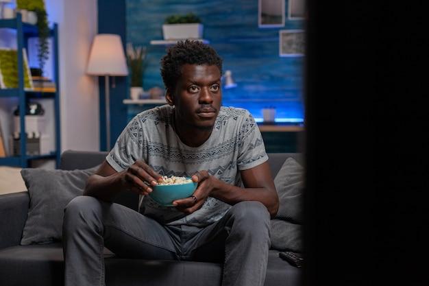 Afroamerikanischer junger mann, der fußballspiel im fernsehen betrachtet