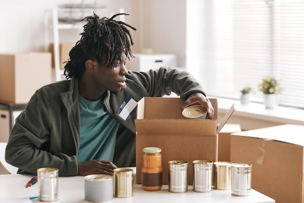 Afroamerikanischer junger mann, der sich freiwillig bei wohltätigkeits- und spendenveranstaltungen meldet, platz kopieren