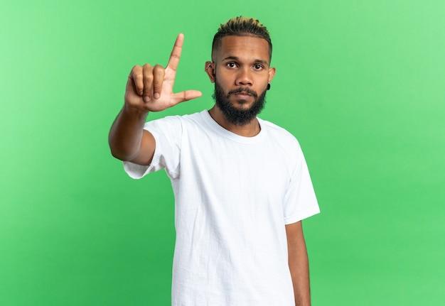 Afroamerikanischer junger mann im weißen t-shirt, der die kamera mit ernstem gesicht anschaut, das den zeigefinger über grünem hintergrund zeigt