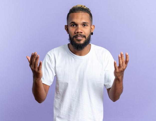 Afroamerikanischer junger mann im weißen t-shirt, der die kamera mit glücklichem gesicht ansieht, das die arme über blauem hintergrund hebt
