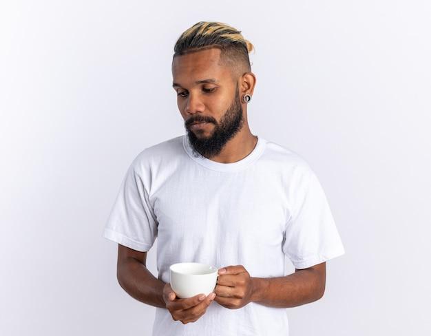 Afroamerikanischer junger mann im weißen t-shirt, der eine tasse heißen tee hält und mit traurigem ausdruck beiseite schaut