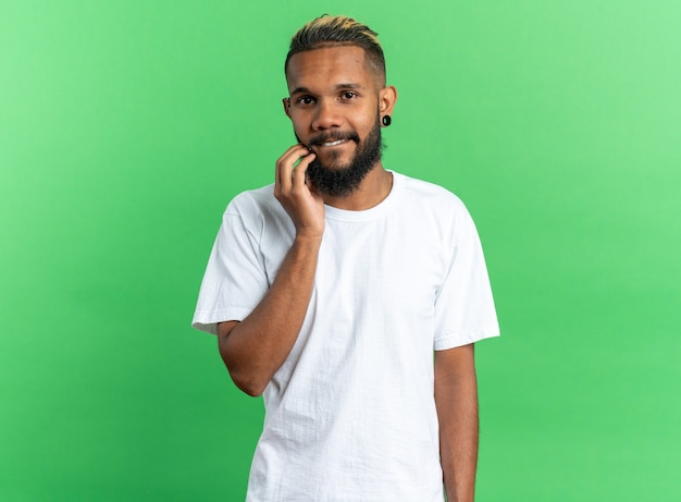 Afroamerikanischer junger mann im weißen t-shirt, der mit der hand am kinn in die kamera schaut und freundlich über grünem hintergrund lächelt