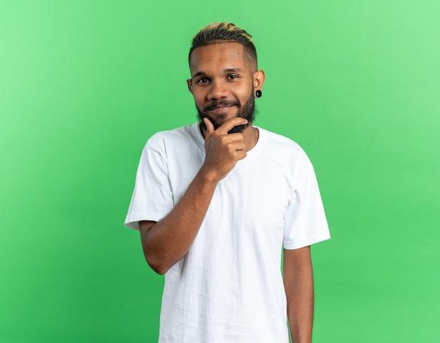 Afroamerikanischer junger mann im weißen t-shirt, der mit der hand am kinn in die kamera schaut und fröhlich über grünem hintergrund steht
