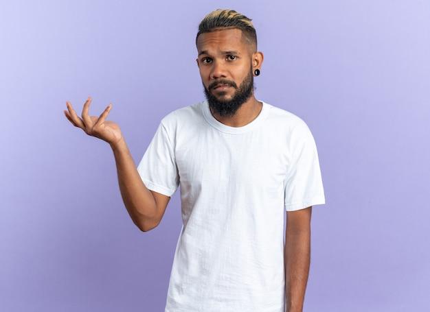 Afroamerikanischer junger mann im weißen t-shirt, der mit verwirrtem ausdruck in die kamera schaut und den arm in empörung auf blauem hintergrund hebt