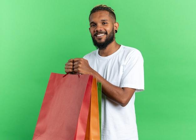 Afroamerikanischer junger mann im weißen t-shirt, der papiertüten hält und in die kamera schaut, fröhlich glücklich und positiv stehend auf grünem hintergrund lächelt